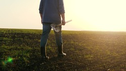 An agronomist man walks through a black plowed field at sunset. Farmer with a shovel in his hands.