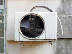 An air conditioner unit with a fan and a drain pipe hangs on the wall outside.