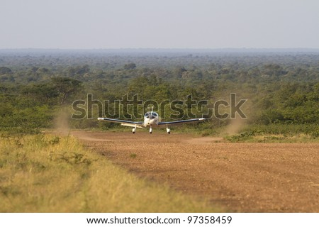 An aircraft landing on a remote dirt airstrip deep in the Botswana bush somewhere between Gabarone and Makgadikgadi.