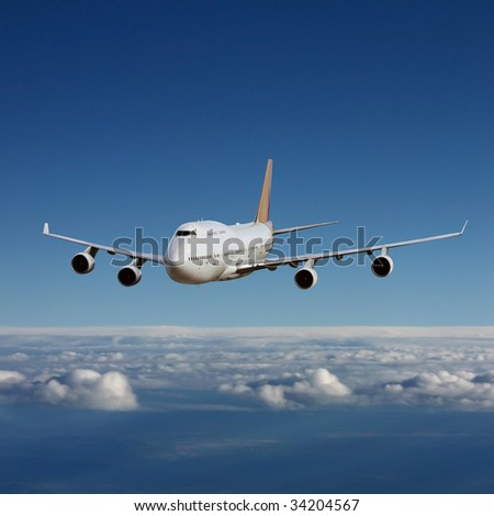An Airliner in Flight over Clouds - stock photo