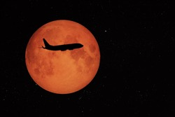 an airplane flying across a full moon