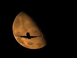 an airplane flying across moon .