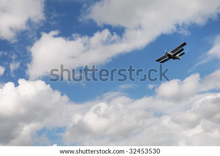 An airplane flying in the blue sky with cumulus clouds