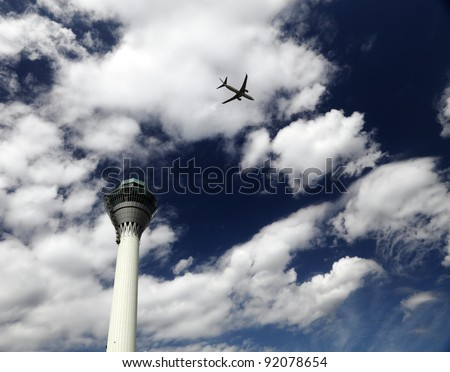 An airplane flying overhead across an airport control tower against a blue cloudy sky.