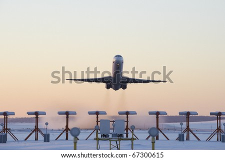 An airplane taking off on a cold winters evening