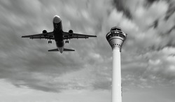An airplane taking off over an airport control tower.