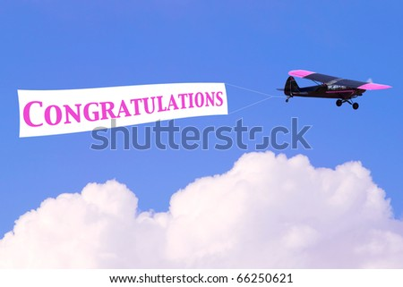 An airplane towing a banner with the word Congratulations in pink, good for female related themes or birth of a baby girl