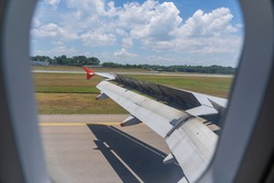 An airplane window view of wing and flaps after landing. Landing aircraft at the airport. Braking of the aircraft on the runway, wing of the plane is in working order. View from window. Close up shot