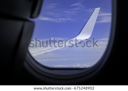 An airplane wing view from window with blue sky and clouds #675248902