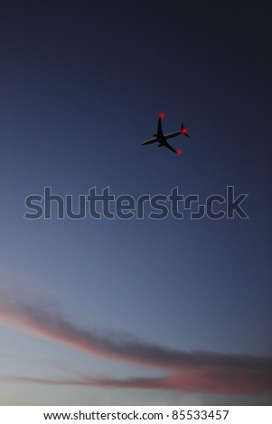 An airplane with blinking tail-light flying high over a surreal evening sky.