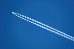 An Airplane with contrail high in the sky