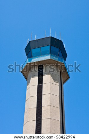 An airport control tower against a blue sky
