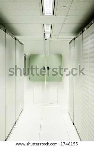 An aisle of racks in a modern datacenter.  Power distribution boards are mounted on the wall at the end.