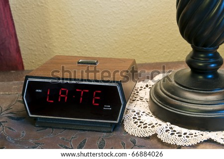 "An alarm clock displaying the word ""late"". This could mean late for work, late for school, late for an appointment or meeting, etc."