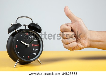 an Alarm Clock with a hand showing success sign