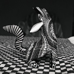 An Alebrije, a traditional mexican handcraft of fantastic animals with vivid and crazy colors. A colorful wolf piece of art. BLack and white