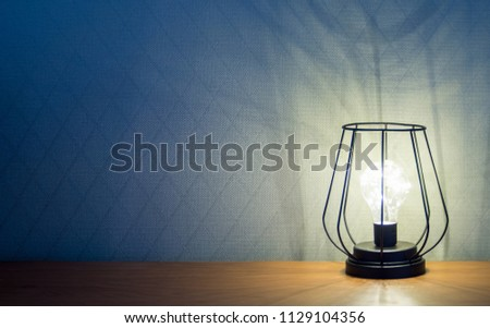 an alight lamp in black wire frame in loft style on wooden table against wall with rhombus pattern copy space #1129104356