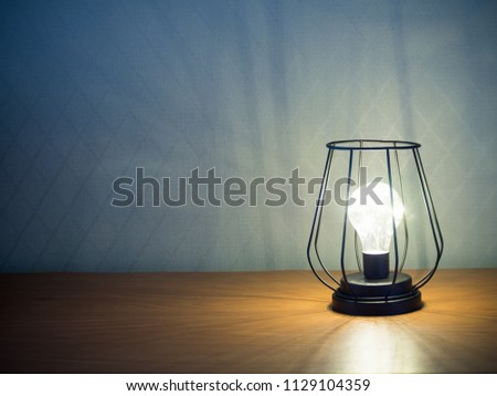 an alight lamp in black wire frame in loft style on wooden table against wall with rhombus pattern copy space #1129104359