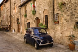 An alley of an Italian medieval village with an old car parked (Gubbio, Umbria, Italy)