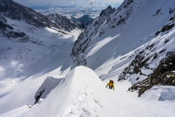 An alpine climber climbing a steep snow gully with an alpine walley, peaks and summits in the background. Winter alpine mountain landscape, extreme winter mountaineering. Adventure ascent, High Tatras