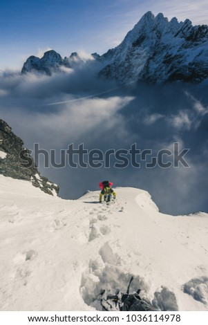 An alpinist climbing a steep snow slope above low clouds in alpine like winter landscape. Winter mountains with snow, high peaks and summits. Climber on an adventure ascent. Winter climbing. #1036114978