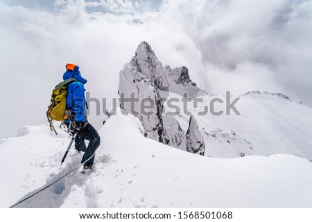 An alpinist climbing an alpine ridge in winter extreme conditions. Adventure ascent of alpine peak in snow and on rocks. Climber ascent to the summit. Winter ice and snow climbing in mountains. Stockfoto ©