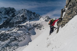 An alpinist climbing in winter alpine like landscape of High Tatras, Slovakia. Winter mountaineering in snow, ice and rock. Alpinism, high peaks and summits with snow and ice.