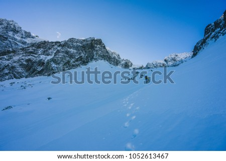 An alpinist on an adventure ascent in winter alpine like landscape of High Tatras, Slovakia. Climber climbing steep snow and ice slopes of a mountain. Ascent to a summit of a peak. #1052613467