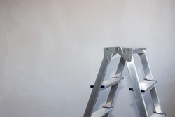 an aluminum stepladder stands against a gray wall. Repair and improvement of housing. Copy space to the left.