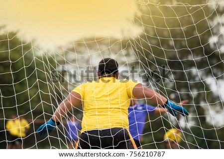An amateur goalkeeper prepares to make a save from an oncoming  shot at goal, during a soccer game.