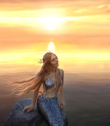 an amazing golden-haired mermaid on the stone in the evening lights of sun