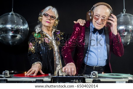 an amazing grandma and grandpa, older couple djing and partying in a disco setting