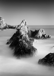 An amazing grayscale shot of a rocky beach in Guernsey