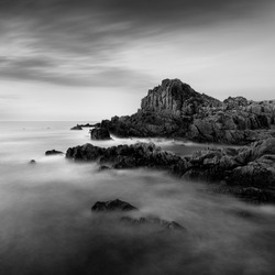 An amazing grayscale shot of a rocky beach in Guernsey near the Fort Houmet