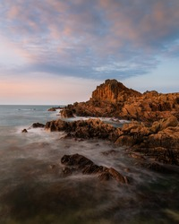 An amazing shot of a rocky beach near Fort Houmeton a sunset background in Guernsey
