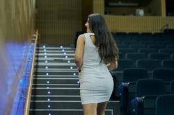 An amazing shot of a young female posing in a cinema hall