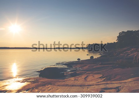 An amazing sunset by the sea. Image taken in Finland during summer evening. Image has a vintage effect applied and some windmills are in the background.