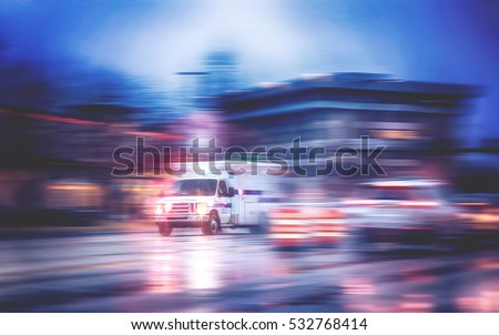 an ambulance racing through the rain on a stormy night with motion blur (NO SHARP FOCUS DUE TO RAIN) with reflections in the road