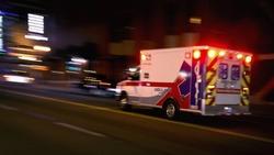 An ambulance speeding through traffic at nighttime