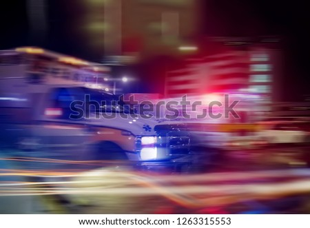 An ambulance speeding through traffic at nighttime  #1263315553