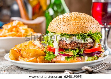 An american burger with fried potatoes on the white plate.