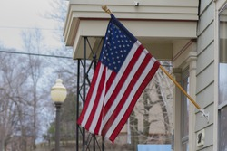 An American flag being proudly placed outside an American home.