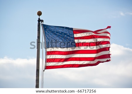 An American flag blowing in the wind and backlit from the sun
