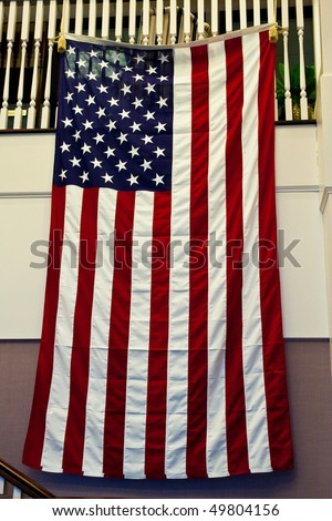 An American Flag hanging from a staircase on an office wall