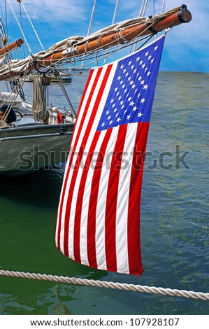 an american flag hanging of the outhaul on a yacht