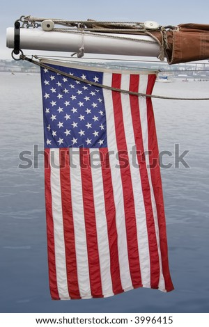 An American flag hanging off the outhaul on a sailing ship.