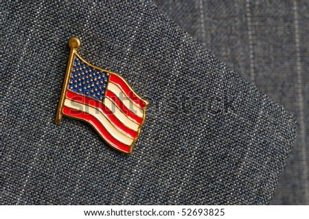 An American flag lapel pin on a pinstripe suit lapel