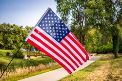 An American flag on display in a public park.  The flag is flying from a small pole at a 45 degree angle, flying left to right, there is parkland, a sidewalk and a small creek in the background.
