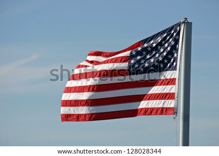 An American flag waving in the wind on a sunny day