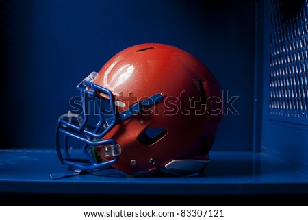 An american football helmet sits in an empty locker. Dramatic lighting.